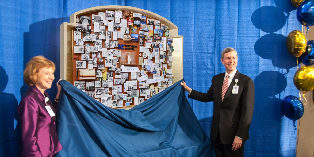 Two people standing next to the Holy Cross collage as a cloth is being removed, revealing the collage to the audience.