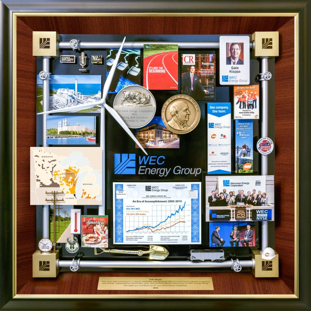 WEC Energy Retirement Gift presented to CEO . Features miniature windmill, Stock Exchange medallion, ID card, growth chart, groundbreaking shovel, miniature hard hat. The border is created with miniature energy pipes. Logo is on the 4 cornerstones.