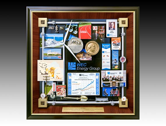 WEC Energy Retirement Gift presented to CEO as gift of appreciation. Features miniature windmill, medallion, ID card, growth chart, miniature hard hat. The border is created with miniature energy pipes.