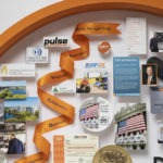 Large collage personalized with over 60 items for the CEO of Discover. Close-up showcases an orange ribbon, printed with the Discover values.