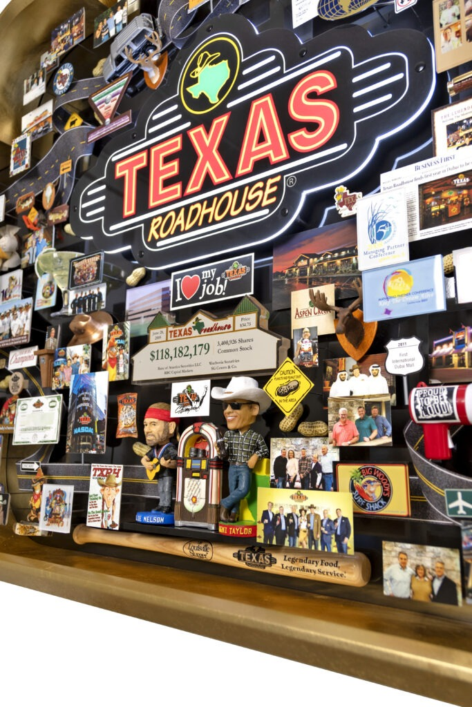 Large collage for Texas Roadhouse featuring bobble head of Willie Nelson next to juke box, Louisville Slugger bat, neon sign.