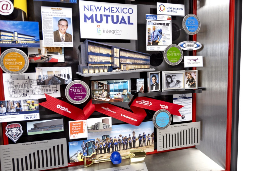 3-dimensional collage gifted to retiring President and CEO. Includes miniaturized photos, publications, and graphs showcasing the company's growth.
