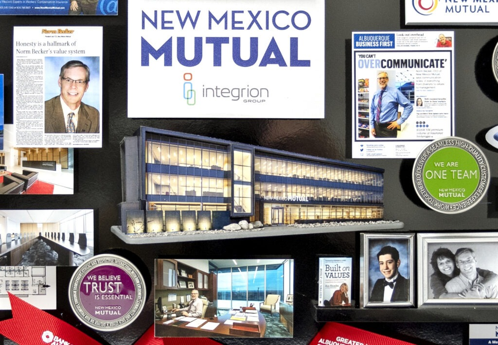 3-dimensional collage containing miniaturized items includes 3D replica of New Mexico Mutual headquarters building.